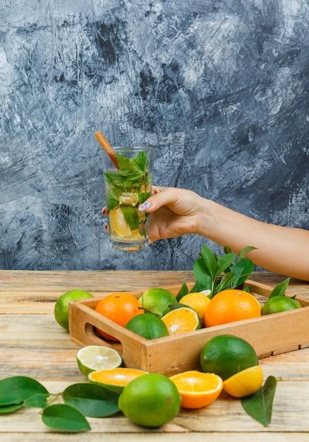 Close-up citrusvruchten in houten kist met gefermenteerde drank Gratis Foto