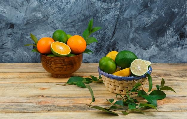 Close-up citrusvruchten in kommen met bladeren op een houten bord Gratis Foto