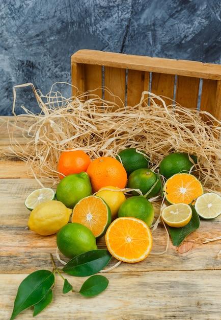 Close-up citrusvruchten met houten kist op een houten bord Gratis Foto
