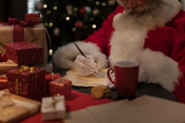 Close-up de kerstman die een brief schrijft Gratis Foto