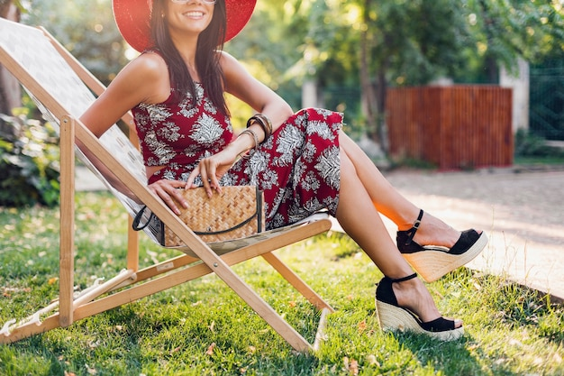 Close-up details benen dragen wiggen sandaal schoenen, schoeisel, stijlvolle mooie vrouw zittend in een ligstoel in tropische stijl outfit, zomer modetrend, stro handtas, accessoires, vakantie Gratis Foto