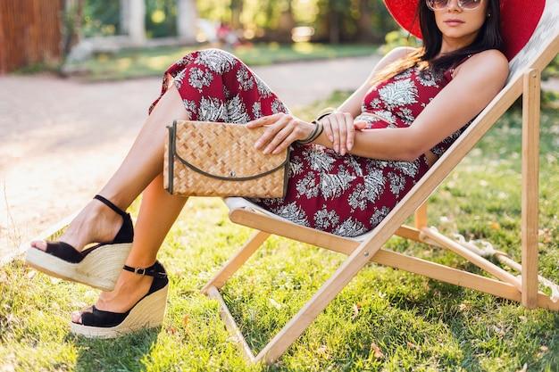 Close-up details benen dragen wiggen sandaal schoenen, schoeisel. stijlvolle mooie vrouw zittend in een ligstoel in tropische stijl outfit, zomer modetrend, stro handtas te houden. Gratis Foto