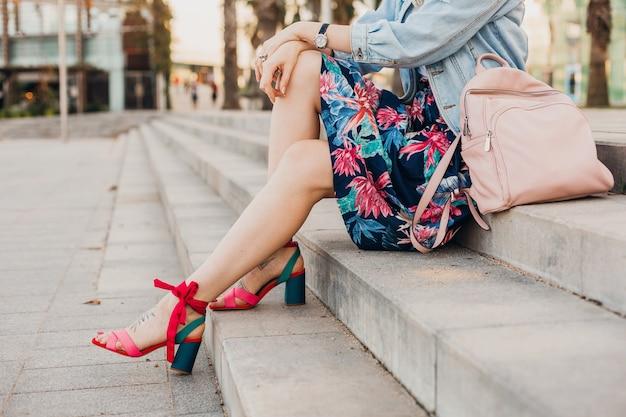 Close-up details van benen in roze sandalen van vrouw zittend op trappen in stad straat in stijlvolle bedrukte rok met lederen rugzak, zomer stijl trend Gratis Foto