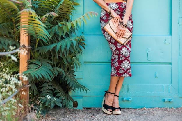 Close-up details van schoenen sandalen op een wig van stijlvolle mooie vrouw poseren op blauwe muur, zomerstijl, modetrend, rok, mager, stro handtas, accessoires, tropische vakantie, benen Gratis Foto