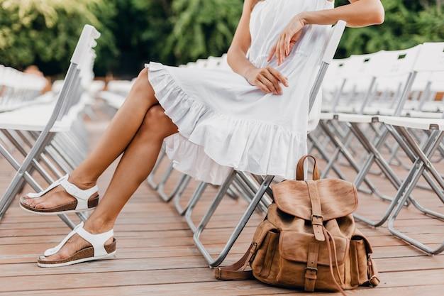 Close-up details van vrouw gekleed in witte jurk zittend in zomer openluchttheater op stoel alleen lente streetstyle modetrend, accessoires, reizen met rugzak, magere benen in sandalen Gratis Foto