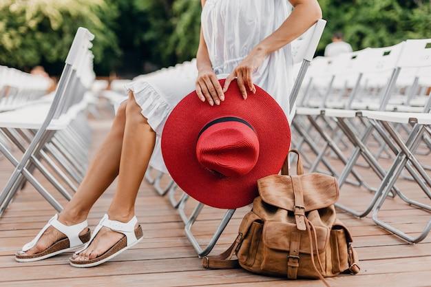 Close-up details van vrouw in witte jurk, rode hoed zitten in zomer openluchttheater op stoel alleen lente streetstyle modetrend, accessoires, reizen met rugzak, magere benen in sandalen Gratis Foto