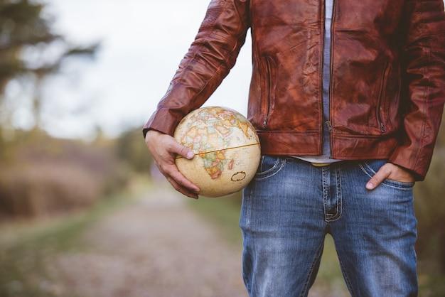 Close-up die van een mannetje is ontsproten dat een leerjasje draagt dat een bureaubol met een vage achtergrond houdt Gratis Foto