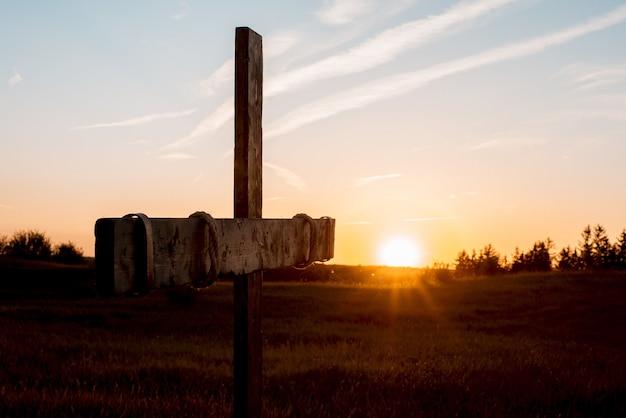 Close-up die van een met de hand gemaakt houten kruis op een grasrijk gebied is ontsproten met de zon die op de achtergrond glanst Gratis Foto