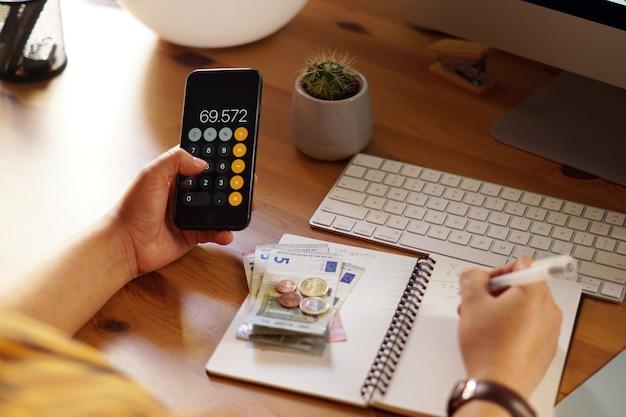 Close-up die van een ondernemer is ontsproten die vanuit huis aan zijn persoonlijke financiën en besparingen werkt Gratis Foto