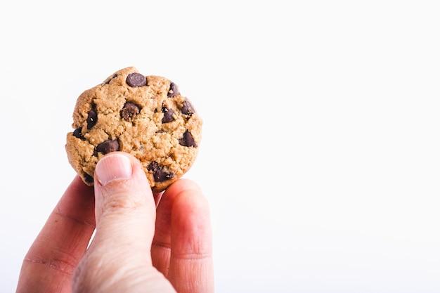 Close-up die van een persoon is ontsproten die een chocoladeschilferkoekje houdt dat op wit wordt geïsoleerd Gratis Foto