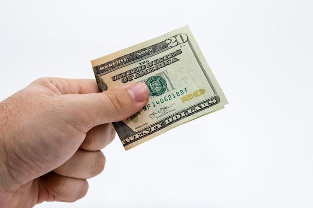 Close-up die van een persoon is ontsproten die een dollarrekening over een wit houdt Gratis Foto