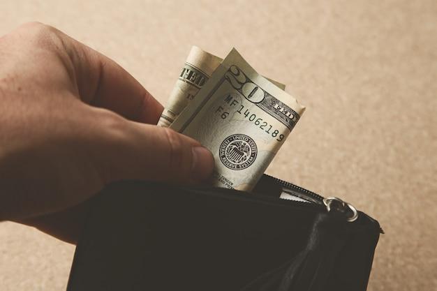 Close-up die van een persoon is ontsproten die wat geld in zijn leerportefeuille steekt Gratis Foto