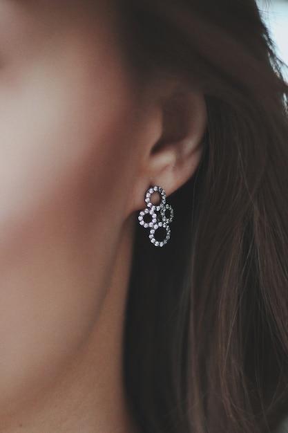 Close-up die van een vrouw is ontsproten die een mooie hangeroorbel draagt Gratis Foto