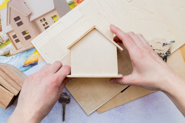 Close-up die van hand houten miniatuurhuismodel houden Gratis Foto