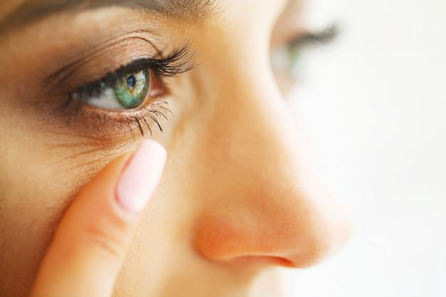 Close-up die van mooie vrouw ooglens in oog toepassen Premium Foto