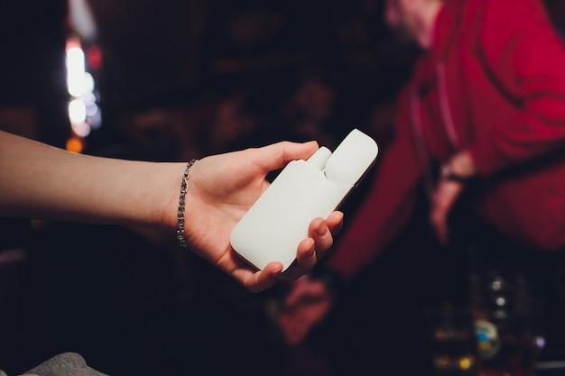 Close-up die van vrouw elektronische sigaret in hand houden. mooi meisje maakt gebruik van een elektronische sigaret. Premium Foto