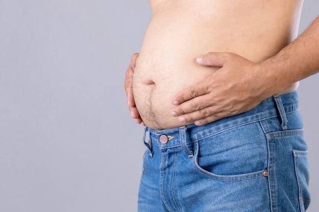 Close-up dikke man staan en zijn buik laten zien. dikke mensen en gezond concept Premium Foto