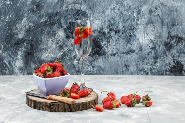 Close-up een kom aardbeien op een houten bord met een glas drank op wit en donkerblauw marmeren oppervlak. horizontaal Gratis Foto