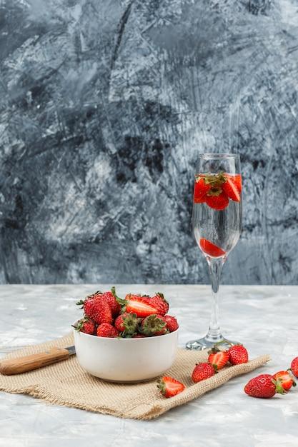 Close-up een kom aardbeien op een stuk zak met een glas drank op wit en donkerblauw marmeren oppervlak. verticaal Gratis Foto