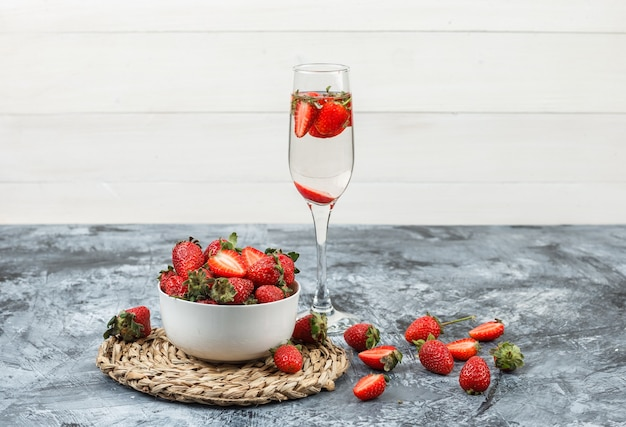 Close-up een kom aardbeien op ronde rieten placemat met een glas drank op donkerblauw marmer en witte houten plank. horizontaal Gratis Foto