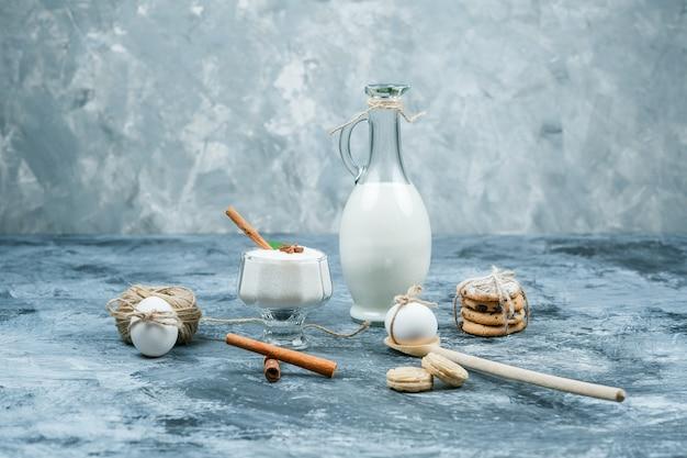 Close-up een kruik melk en een glazen kom yoghurt met koekjes, eieren, kluwen en kaneel op donkerblauw en grijs marmeren oppervlak. horizontaal Gratis Foto