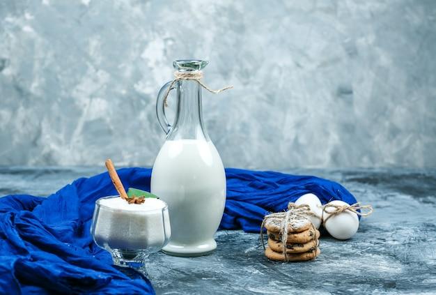 Close-up een kruik melk met blauwe sjaal, chocoladeschilferkoekjes en witte koekjes en een glazen kom yoghurt op donkerblauw en grijs marmeren oppervlak. horizontaal Gratis Foto
