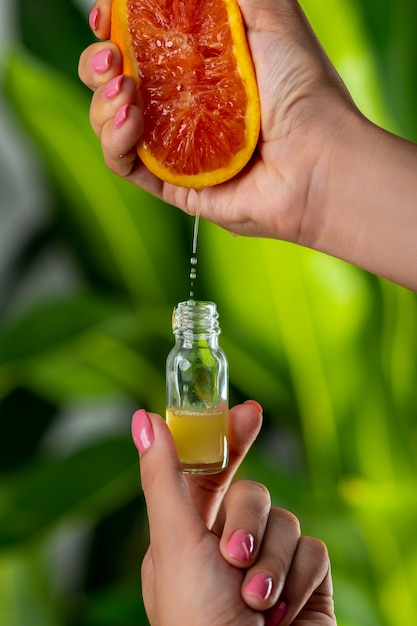 Close-up: een vrouwelijke hand drukt grapefruitsap in een glazen fles Premium Foto