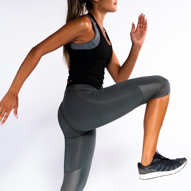 Close-up fit meisje met een been omhoog Gratis Foto