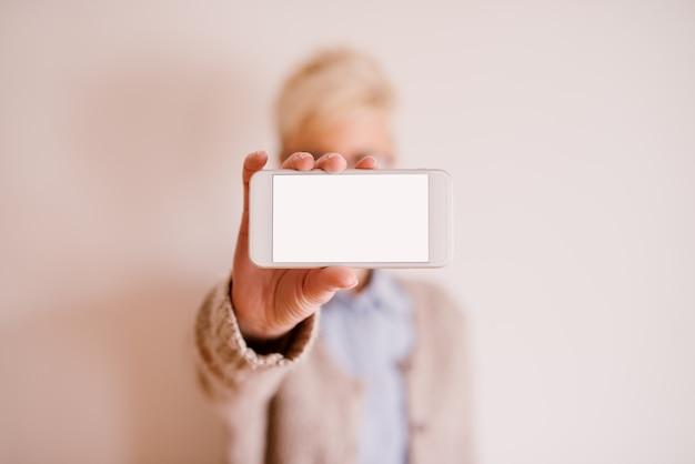 Close-up focus weergave van mobiel in een horizontale positie met een witte bewerkbare scherm terwijl een wazige vrouw het vasthoudt. Premium Foto