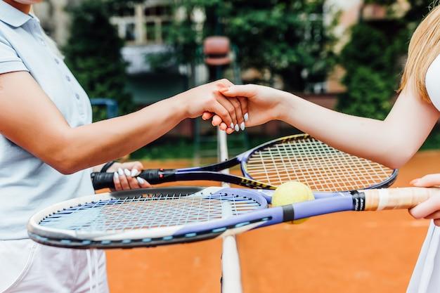 Close-up foto. handenmeisjes die handen op tennisbaan, team schudden. werk en speel samen. Premium Foto