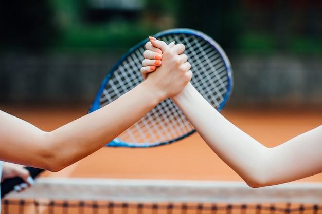 Close-up foto. jonge meisjes die handen op tennisbaan, het glimlachen schudden. Premium Foto
