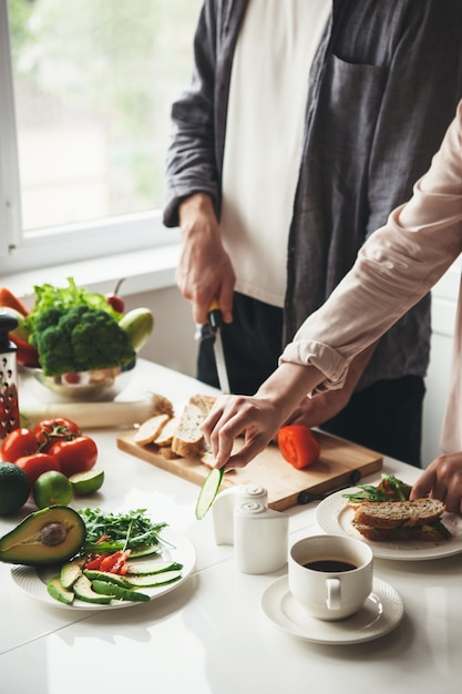 Close-up foto van een paar voorbereiding ontbijt samen in de keuken brood en groenten snijden Premium Foto