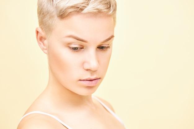 Close-up foto van ernstige doordachte jonge blonde vrouw met stijlvol kort kapsel met peinzende gezichtsuitdrukking. leuk mooi meisje met perfecte pure huid poseren geïsoleerd, naar beneden te kijken Gratis Foto