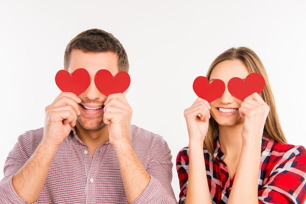 Close-up foto van gelukkige paar verliefd ogen verbergen achter papieren harten Premium Foto