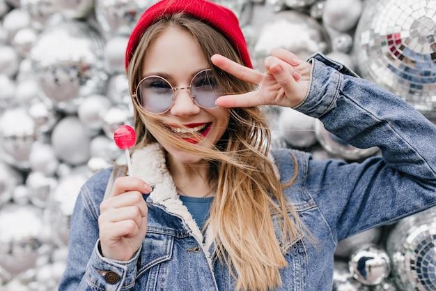 Close-up foto van prachtige blonde meisje met blij gezicht expressie poseren met discoballen. portret van knappe dame in de rode lolly van de hoedenholding op stedelijke muur. Gratis Foto