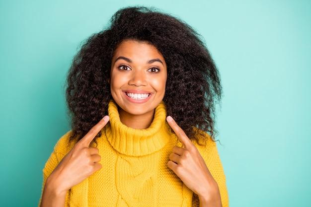 Close-up foto van verbazingwekkende donkere huid krullende dame wijzende vingers op perfecte tanden adviseren tandarts dragen gele gebreide trui geïsoleerde blauwe wintertaling kleur muur Premium Foto