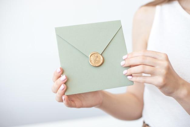 Close-up foto van vrouwelijke handen met uitnodiging envelop met een lakzegel, cadeaubon, briefkaart, bruiloft uitnodigingskaart. Premium Foto
