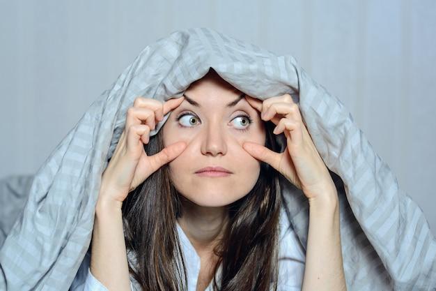 Close-up frontaal portret van een vrouw die haar ogen met haar handen houdt, die aan slapeloosheid lijden. angst, nachtmerries, gluren, je zien, kijken Premium Foto