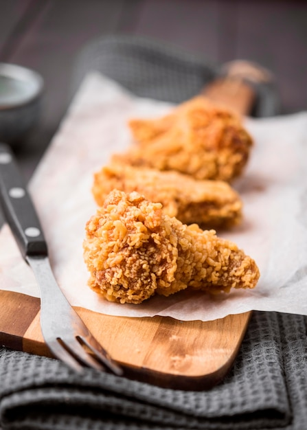 Close-up gebakken kippenvleugels op snijplank met vork Gratis Foto