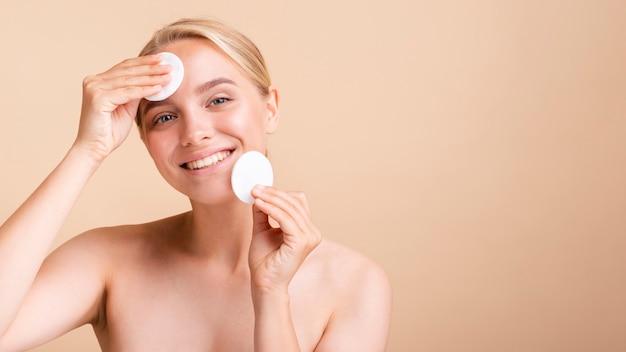 Close-up gelukkig blond model met wattenschijfjes Gratis Foto