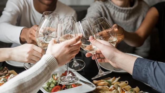 Close-up gelukkige vrienden die glazen wijn roosteren Gratis Foto