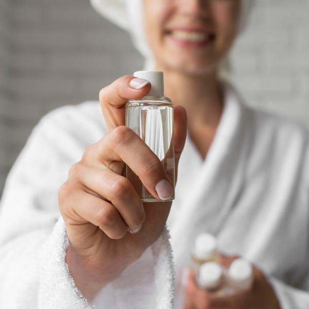 Close-up gelukkige vrouw met kleine fles Gratis Foto