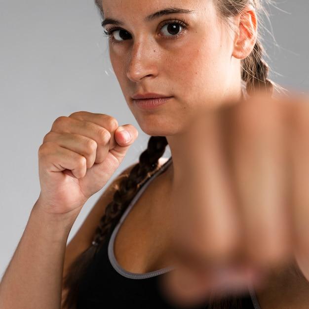 Close-up geschikte vrouw in gevechtspositie met vage hand Gratis Foto