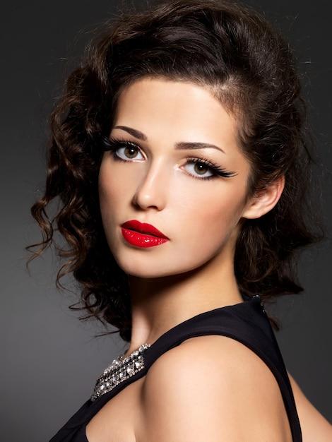 Close-up gezicht van brunette vrouw met mode make-up en rode lippen Gratis Foto
