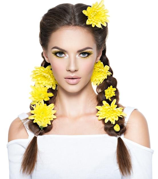 Close-up gezicht van een jonge mooie vrouw met heldere gele make-up. mode portret. aantrekkelijk meisje met stijlvol kapsel, vlechten - geïsoleerd op wit. professionele make-up. kunst kapsel. Gratis Foto