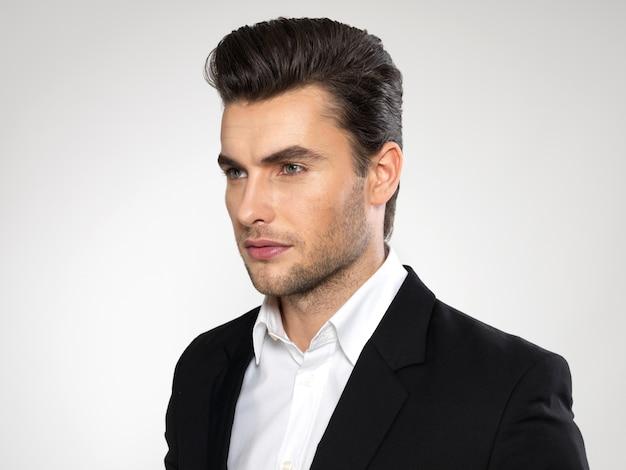 Close-up gezicht van een mode jonge zakenman in zwart pak casual poses in de studio Gratis Foto