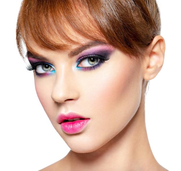 Close-up gezicht van een mooie vrouw met heldere, levendige make-up. mannequin met creatieve oogmake-up - die op wit wordt geïsoleerd. meisje met een gemberhaar. kort kapsel met pony Gratis Foto
