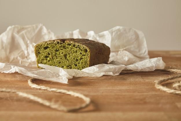 Close-up gezond dieet groen brood van spinash deeg op ambachtelijke papier geïsoleerd op een houten bord Gratis Foto