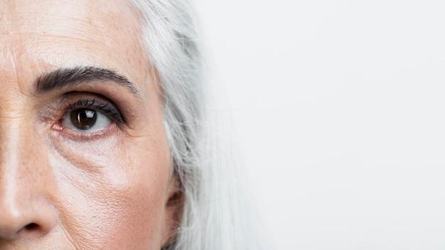 Close-up half gezicht van hogere vrouw Gratis Foto