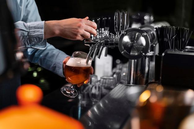 Close-up hand bier gieten in glas Gratis Foto